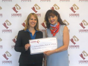 Adele Connors, ACT Director of Development, receives a $3,000 check from Kristin Lumley, Assistant General Manager at Legends Casino